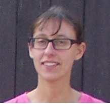 a white woman wearing glasses and a pink shirt in front of a brown background