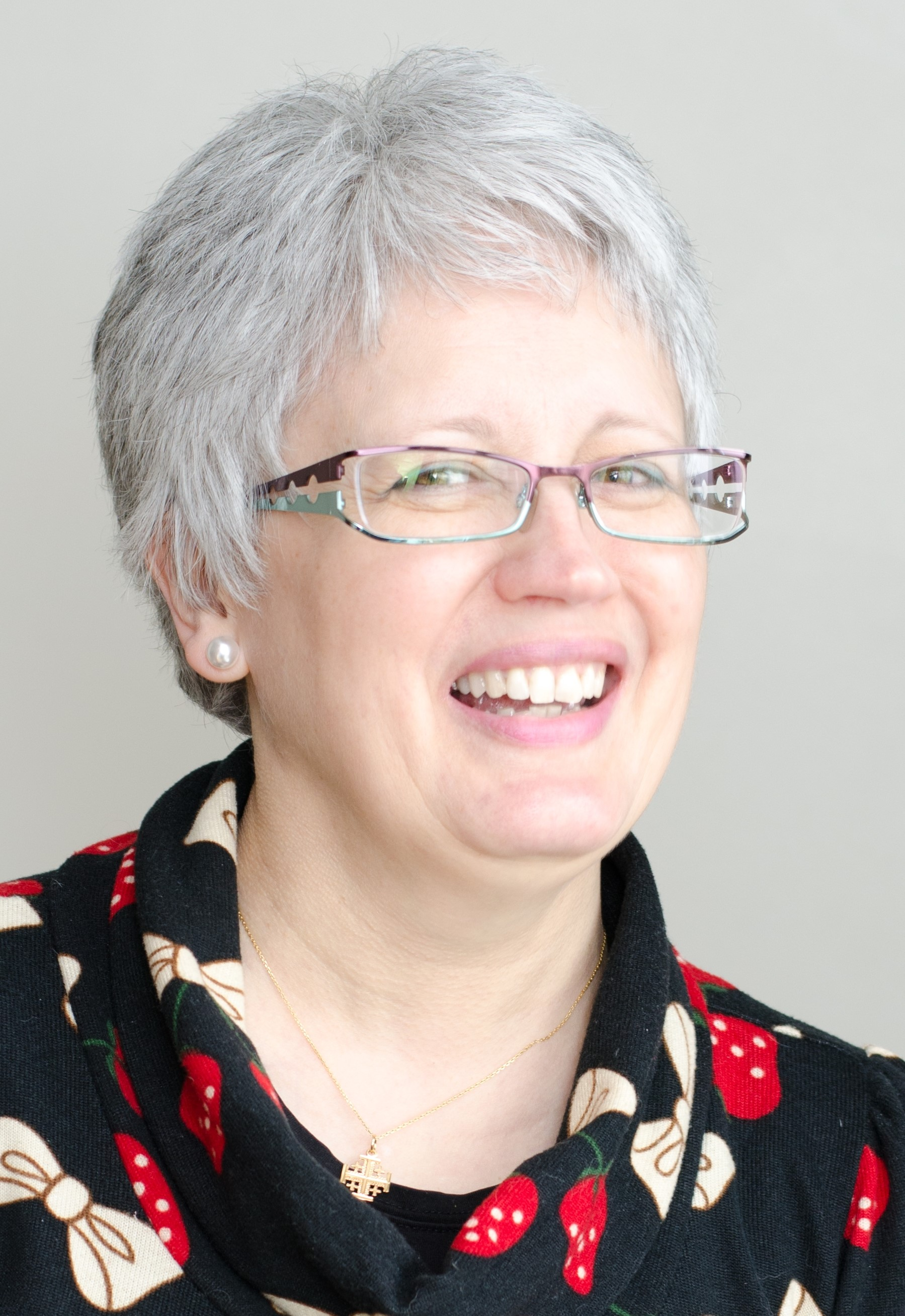 A white woman with grey hair and glasses, wearing a black top with white-and-red patterns, smiles against a pale grey background.