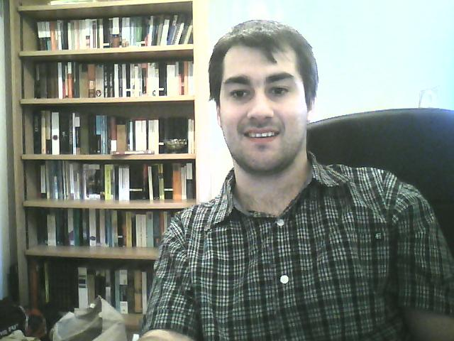 An image of Benjamin Wood, smiling in front of a bookcase.